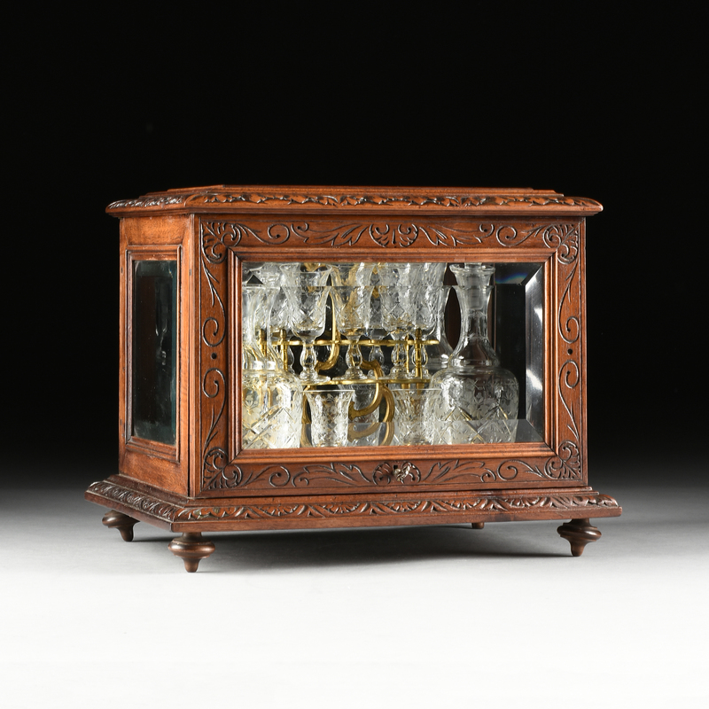 A LATE VICTORIAN CARVED WALNUT AND BEVELED GLASS TANTALUS, LATE 19TH/EARLY 20TH CENTURY,